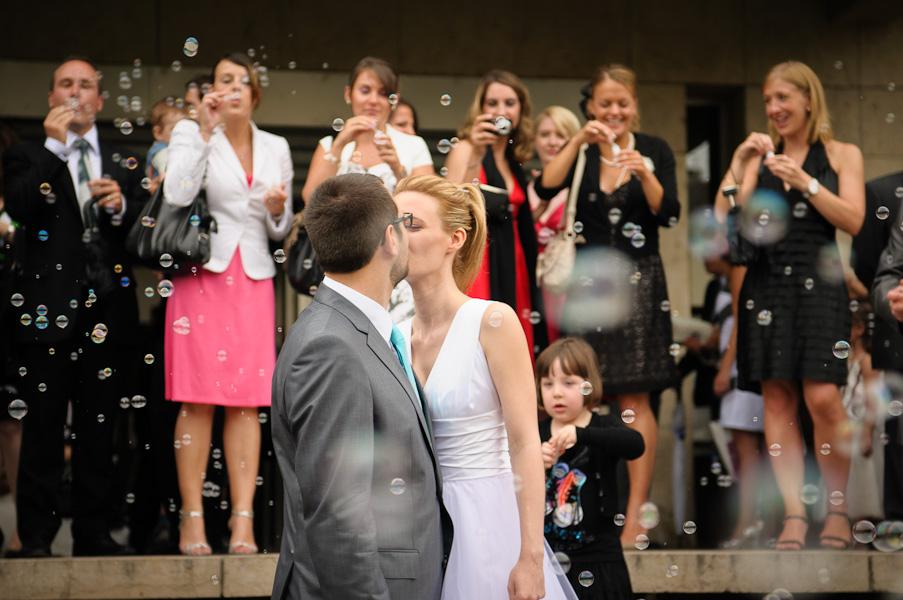 Portrait des mariés s'embrassant sur les marches de la marie sous une tempète de bulles soufflées par leurs invités en arrière plan