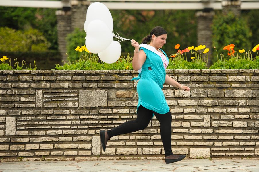 Portrait d'une jeune fille en fuite portant des ballons blancs