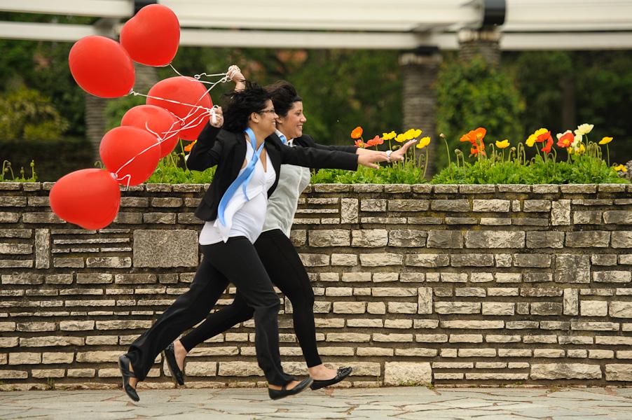 Portrait de deux jeunes femmes déguisées en homme poursuivant quelqu'un avec des ballons rouges à la main