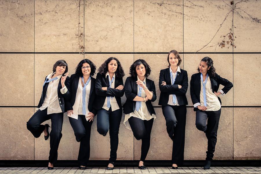 Portrait d'un groupe de six filles en costard cravatte adossées virilement à un mur
